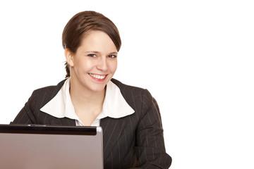 Junge Frau sitzt glücklich im Büro und arbeitet am Computer