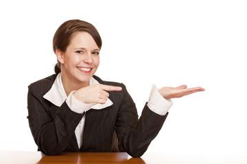 Junge attraktive Frau zeigt mit Finger auf Werbefläche