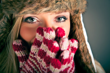 Portrait of beautiful blond woman in warm clothes on blue