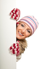 Woman in colorful hat and gloves peeping from behind whiteboard