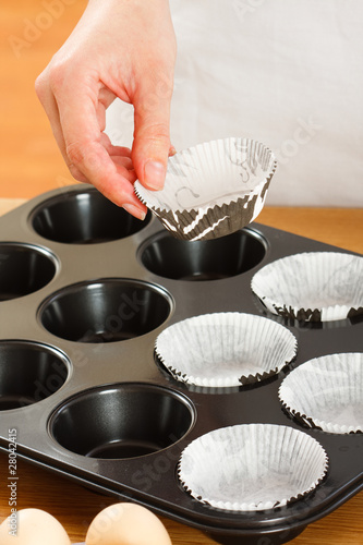 A female cook 's hand putting  muffin cups in the oven pan.