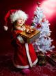 Kind mit dem Geschenkbox unter dem Christbaum