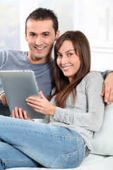 Couple sitting on sofa with electronic pad