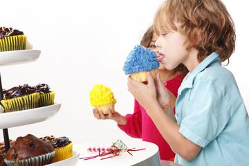 A couple of kids enjoy cupcakes