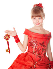 Child in long red dress holding christmas key.