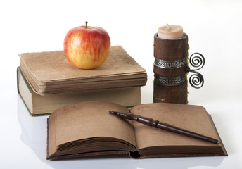 books, notebook, candle and an apple on a white background