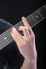 Human hand taking  A-major accord at guitar