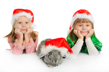 Two girls with a rabbit in caps of Santy on a white background