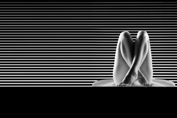 black and white artistic nude, with crossed legs, shot on stripe