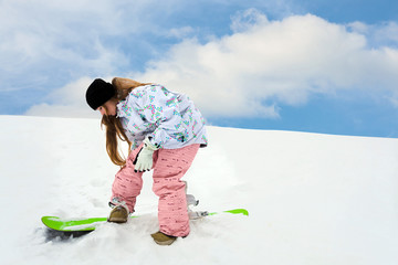 Young girl close snowboard fastering