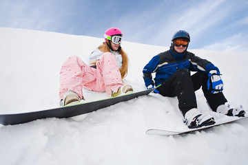 Two person sit on snow and preparing to ride