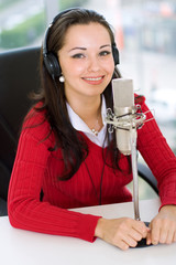 A woman DJ is in front of a mic in the broadcasting studio
