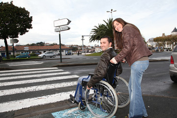 Woman helping friend in wheelchair cross the street
