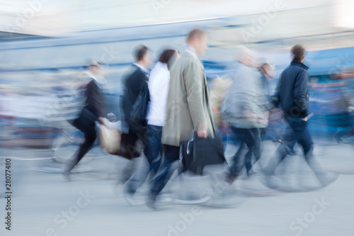 Motion blurred people rushing to work
