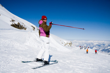 Woman skier pointing ski slope