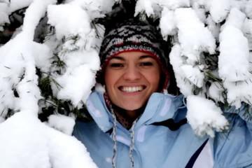 Smiling winter woman look behind tree