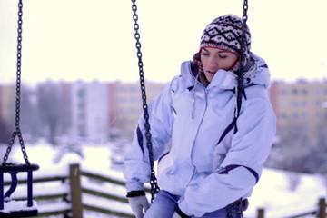 Sad woman sitting on a swing