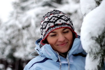 Smiling winter woman look behind tree