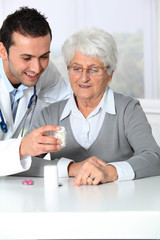 Doctor explaining drugs prescription to elderly woman