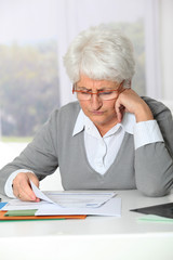 Elderly woman having trouble filling in paperwork