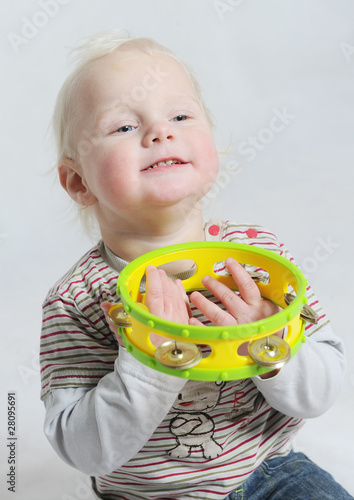 isolated portait baby playing tamborine