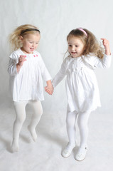 Two happy little girls jumping