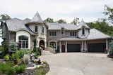 Luxury brick home with two turrets poster