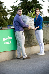 A mid-adult couple recycling garden waste