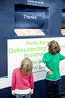 Two young children looking at a recycling container for textiles