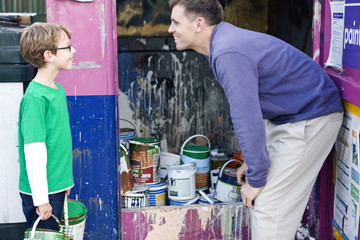 A father and son recycling tins of paint
