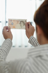 woman checking banknote watermark