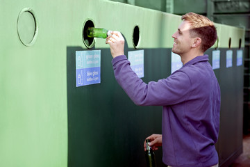 A mid-adult man recycling glass bottles