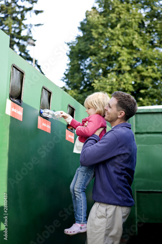 A father and daughter recycling plastic bottles