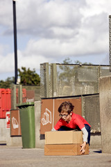 A young boy lifting cardboard boxes in a recycling center