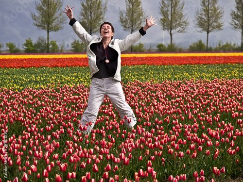 Happy woman jumping in a tulip field