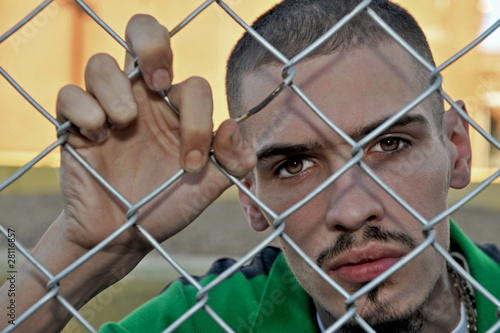 Young Hispanic man struggling to grasp onto a chain link fence.