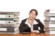 überlastete Frau im Büro zwischen Ordnerstapel denkt nach