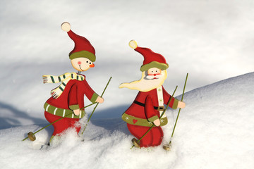 Santa claus and snowman by skiing