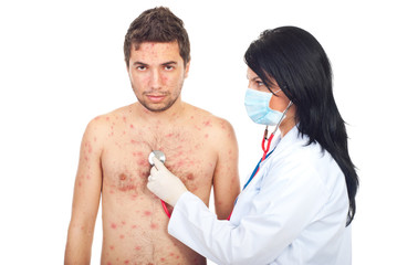 Physician assess man with chickenpox