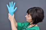 Doctor putting on blue sterilized medical glove poster