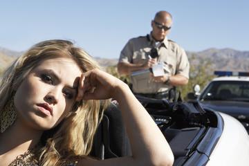 Police officer ticketing women sitting in car
