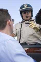 Highway patrol officer examines man's driving license