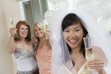 Bride holding champagne, toasting with Friends at Bridal Shower