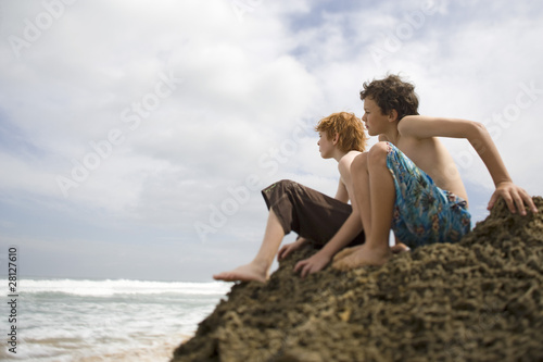 Two pre-teen boys sitting at seashore and watching view