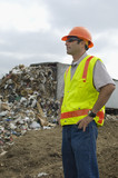 Worker standing near truck dumping waste at landfill site