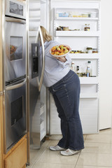 Woman looking into fridge, side view