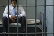 Businessman sitting in prison cell