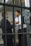 Two men arguing in prison cell