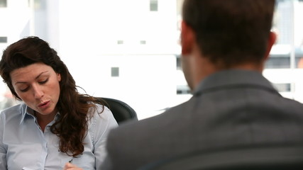 Angry businesswoman during an interview with a man