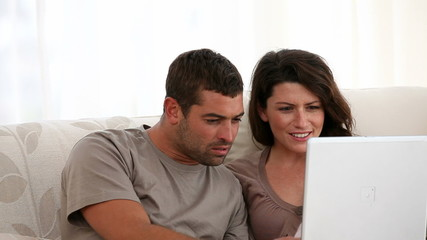 Surprised couple surfing on the web together at home